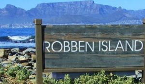 Robben island written on wooden board with mountain in the background