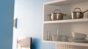 open style kitchen cupboards with pots, plates and glasses
