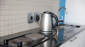 Image of silver kettle next to a 2 plated stove