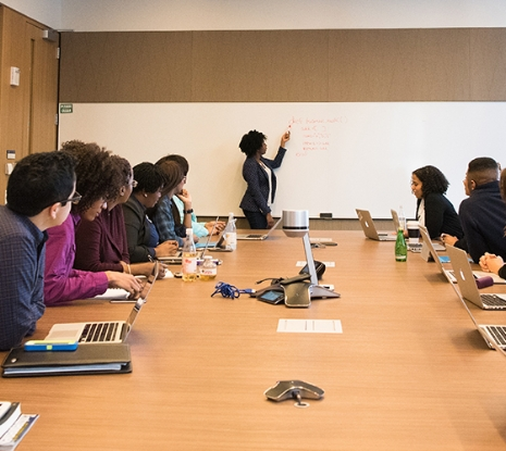 Female writing on a white board in front of team members